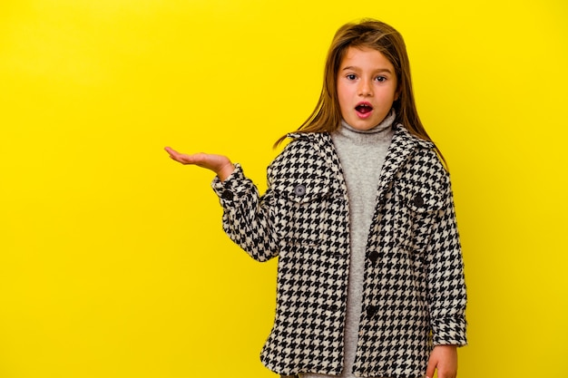 Little caucasian girl isolated on yellow background impressed holding copy space on palm.