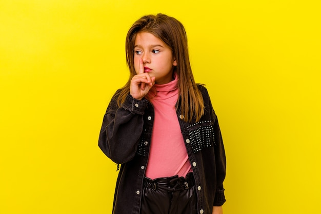 Little caucasian girl isolated on yellow background keeping a secret or asking for silence.