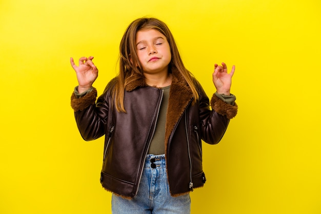 Little caucasian girl isolated on yellow background relaxes after hard working day, she is performing yoga.