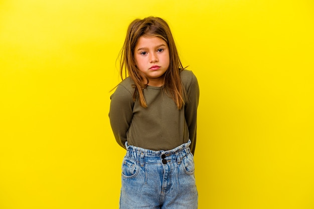 Little caucasian girl isolated on yellow background sad, serious face, feeling miserable and displeased.