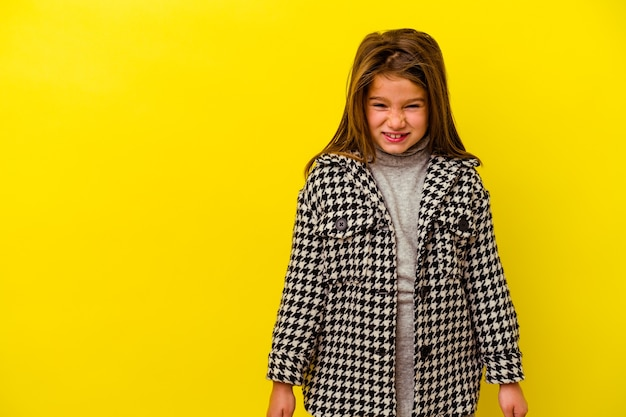 Little caucasian girl isolated on yellow background shouting very angry, rage concept, frustrated.