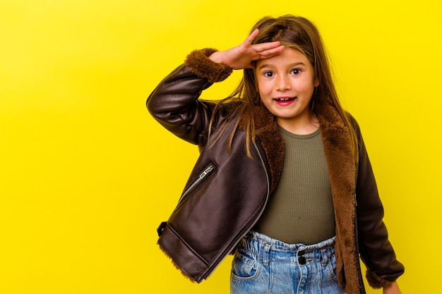 Little caucasian girl isolated on yellow background shouts loud, keeps eyes opened and hands tense.