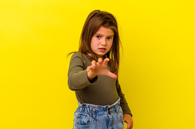 Little caucasian girl isolated on yellow background showing claws imitating a cat, aggressive gesture.