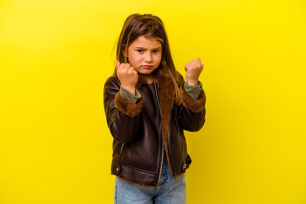 Little caucasian girl isolated on yellow background showing fist to camera, aggressive facial expression.
