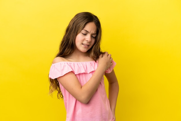 Little caucasian girl isolated on yellow background suffering from pain in shoulder for having made an effort