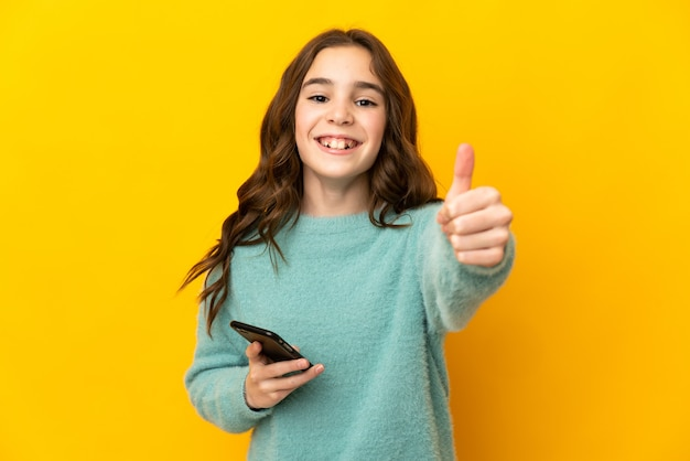 Little caucasian girl isolated on yellow background using mobile phone while doing thumbs up