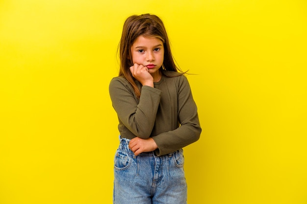 Little caucasian girl isolated on yellow blows cheeks, has tired expression