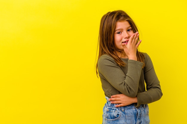 Little caucasian girl isolated on yellow laughing happy, carefree, natural emotion.