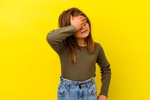 Little caucasian girl isolated on yellow laughs joyfully keeping hands on head. happiness concept.