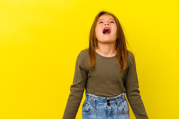 Little caucasian girl isolated on yellow shouting very angry, rage concept, frustrated.