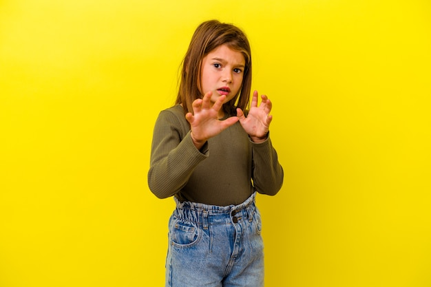 Little caucasian girl isolated on yellow showing claws imitating a cat, aggressive gesture.