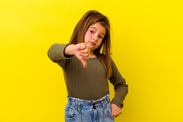 Little caucasian girl isolated on yellow showing thumb down, disappointment concept.