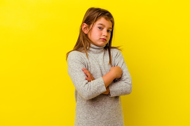 Little caucasian girl isolated on yellow suspicious, uncertain, examining you.