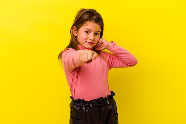 Little caucasian girl isolated on yellow throwing a punch, anger, fighting due to an argument, boxing.
