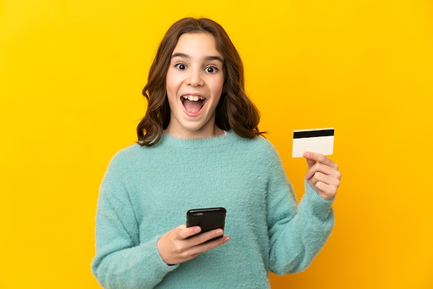Little caucasian girl isolated on yellow wall buying with the mobile and holding a credit card with surprised expression
