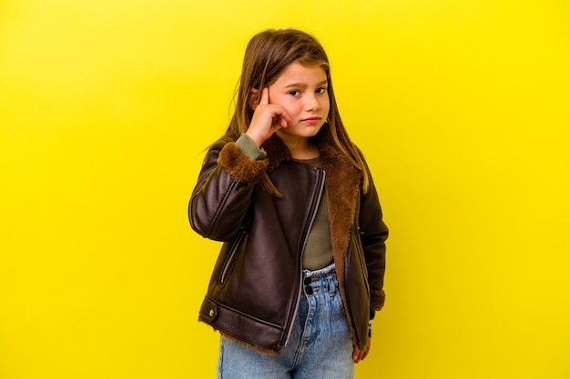 Little caucasian girl isolated on yellow wall covering ears with hands.