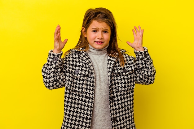 Little caucasian girl isolated on yellow wall screaming with rage.