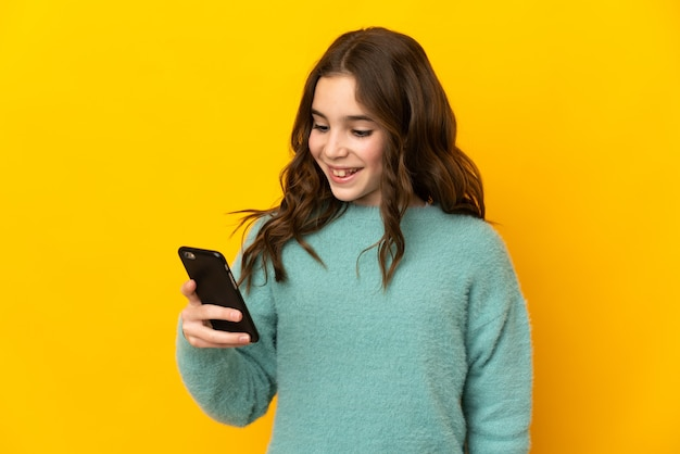 Little caucasian girl isolated on yellow wall sending a message or email with the mobile