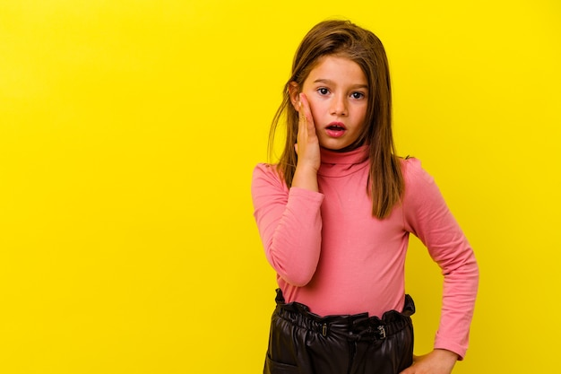 Little caucasian girl isolated on yellow wall shouts loud, keeps eyes opened and hands tense.