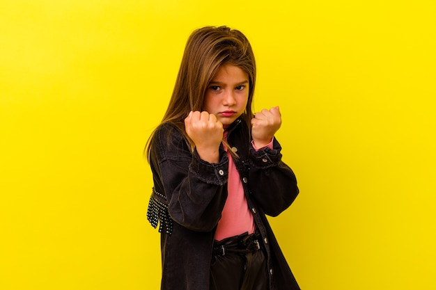Little caucasian girl isolated on yellow wall showing fist to camera, aggressive facial expression.