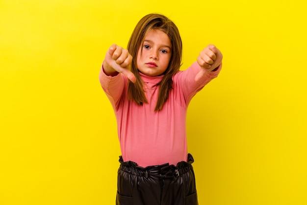 Little caucasian girl isolated on yellow wall showing thumb down and expressing dislike.