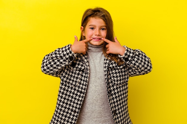 Little caucasian girl isolated on yellow wall smiles, pointing fingers at mouth.
