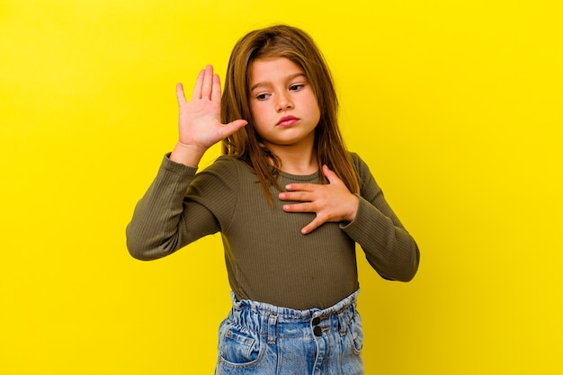 Little caucasian girl isolated on yellow wall taking an oath, putting hand on chest.