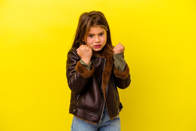 Little caucasian girl isolated on yellow wall upset screaming with tense hands.