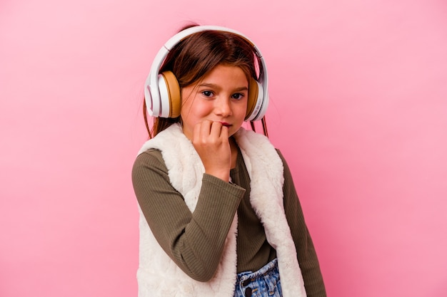 Маленькая кавказская девушка слушает музыку на розовом фоне, кусая ногти, нервная и очень тревожная.
