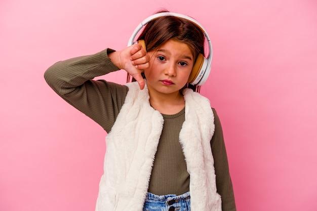 嫌いなジェスチャーを示すピンクの背景に分離された音楽を聞いている小さな白人の女の子は、親指を下に向けます。不一致の概念。