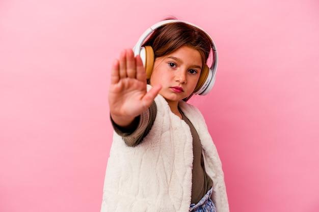 ピンクの背景に孤立した音楽を聞いている小さな白人の女の子は、一時停止の標識を示している手を伸ばして立って、あなたを防ぎます。
