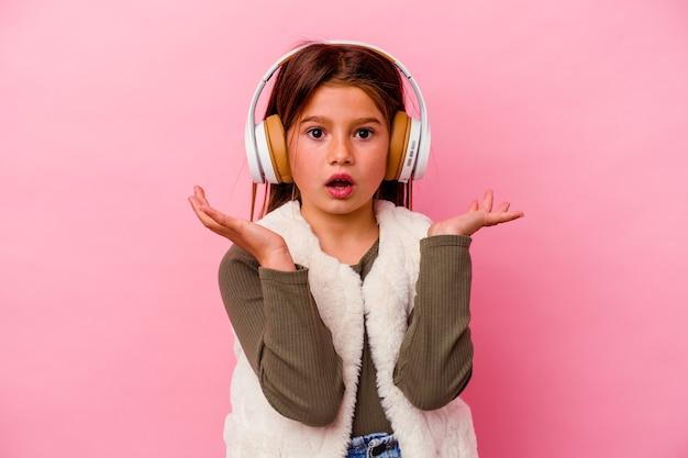 분홍색 벽에 고립 된 작은 있으면 백인 여자 듣기 음악 놀라게 하 고 충격.