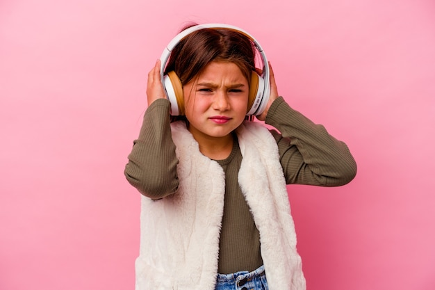 Little caucasian girl listening music isolated on pink covering ears with hands.