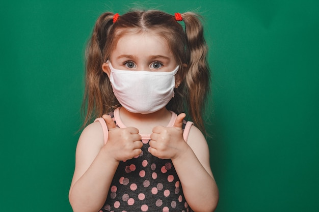 Little caucasian girl in medical mask and polka dot dress showing thumb sign on green background during quarantine and coronavirus pandemic 2020