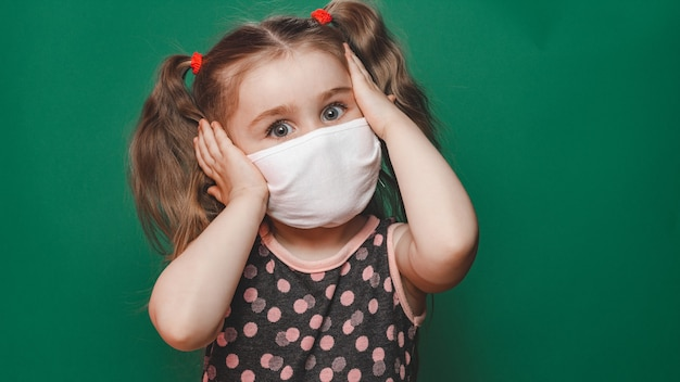 Little caucasian girl in medical mask wears red polka dot dress in studio on green background and holds her head in pain 2020