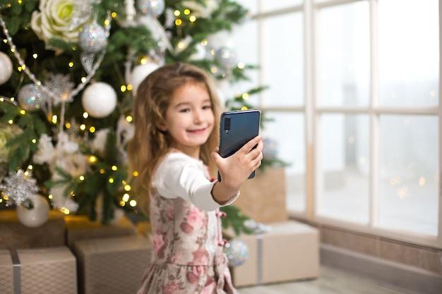 크리스마스 트리의 어린 백인 소녀가 스마트 폰으로 자신의 사진을 찍습니다.