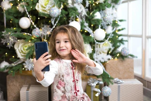 Маленькая кавказская девушка на фоне елки фотографирует себя со смартфоном
