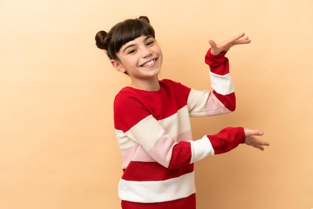 베이지 색 지주 copyspace 광고를 삽입하는 어린 백인 소녀