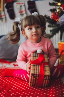 Little caucasian girl in pink sweater with a present in her hands sitting under a new year tree at home
