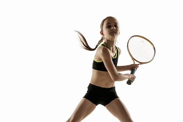 Маленькая кавказская девочка играет в теннис, изолированные на белом фоне