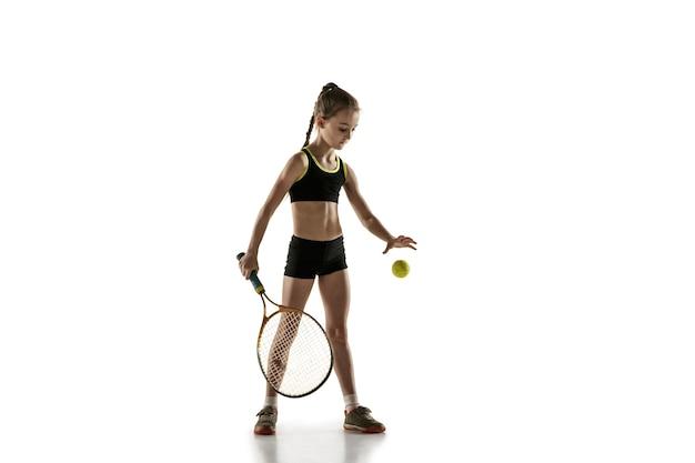 Маленькая кавказская девочка играет в теннис, изолированную на белой стене