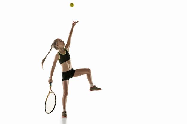 Piccola ragazza caucasica giocando a tennis isolato sul muro bianco