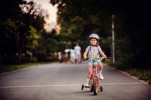 Маленькая кавказская девочка катается на велосипеде в детских кроссовках шлема в летнем парке