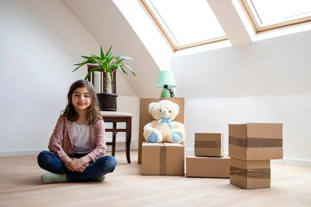 골판지 상자 꽃과 장난감을 배경으로 새 방에 앉아 있는 백인 소녀
