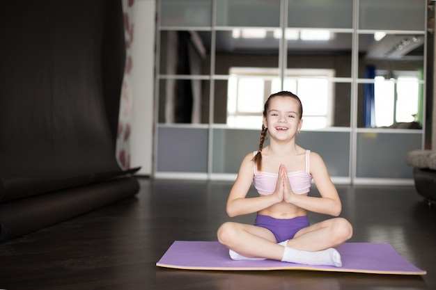 Little caucasian girl sitting on mat in yoga pose and meditating.