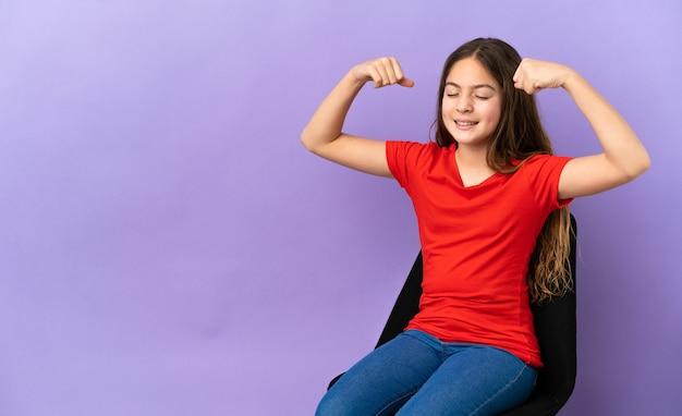 強いジェスチャーをしている紫色の背景で隔離の椅子に座っている小さな白人の女の子