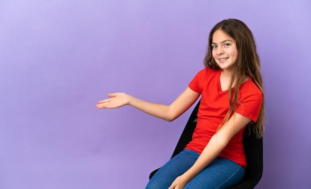 紫色の背景で隔離の椅子に座っている小さな白人の女の子は、来て招待するために手を横に伸ばします