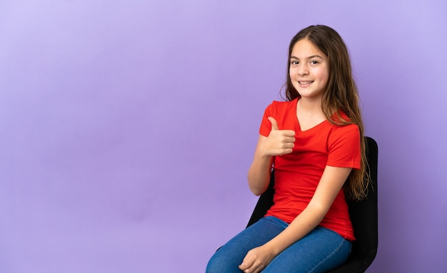 親指を立てるジェスチャーを与える紫色の背景で隔離の椅子に座っている小さな白人の女の子