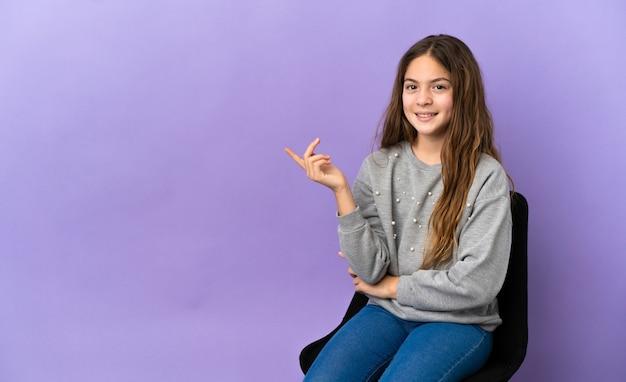 보라색 배경에 격리된 의자에 앉아 행복하고 위를 가리키는 백인 소녀