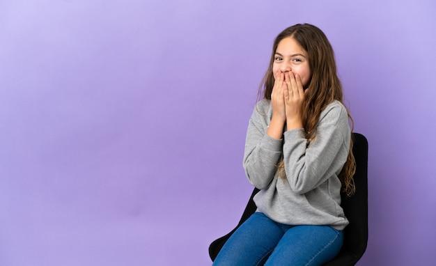 紫色の背景で隔離の椅子に座っている小さな白人の女の子幸せと笑顔の手で口を覆う